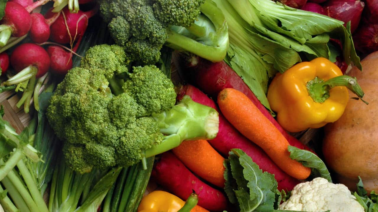 Variety of vegetables includes: radishes, broccoli, green onions, red onions, carrots, romaine lettuce, yellow peppers, and cauliflower.