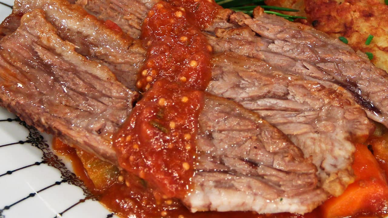 Three thin slices of beef brisket with braising juices and tomato sauce.