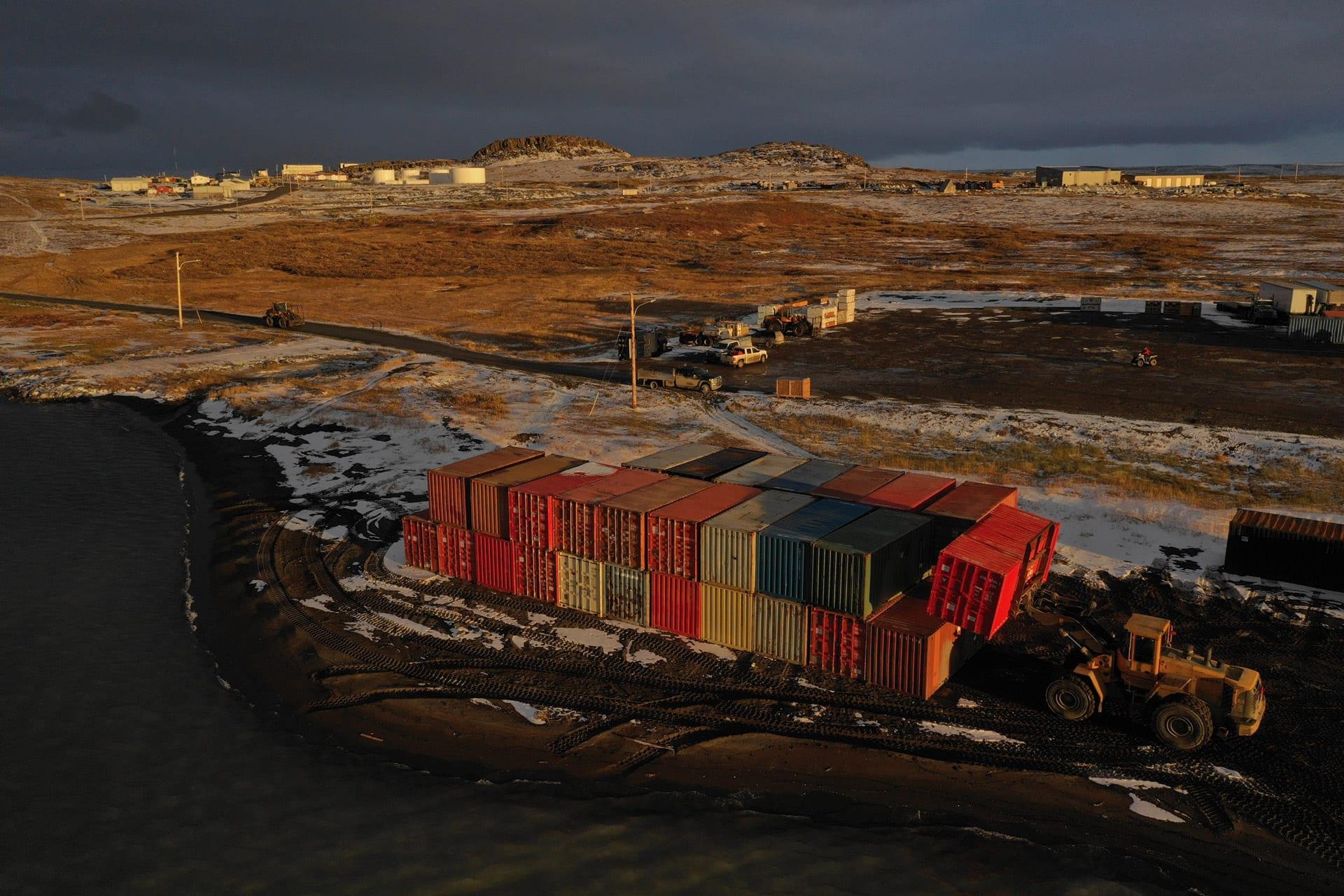 Cargo loader piling up seacans in Kugluktuk