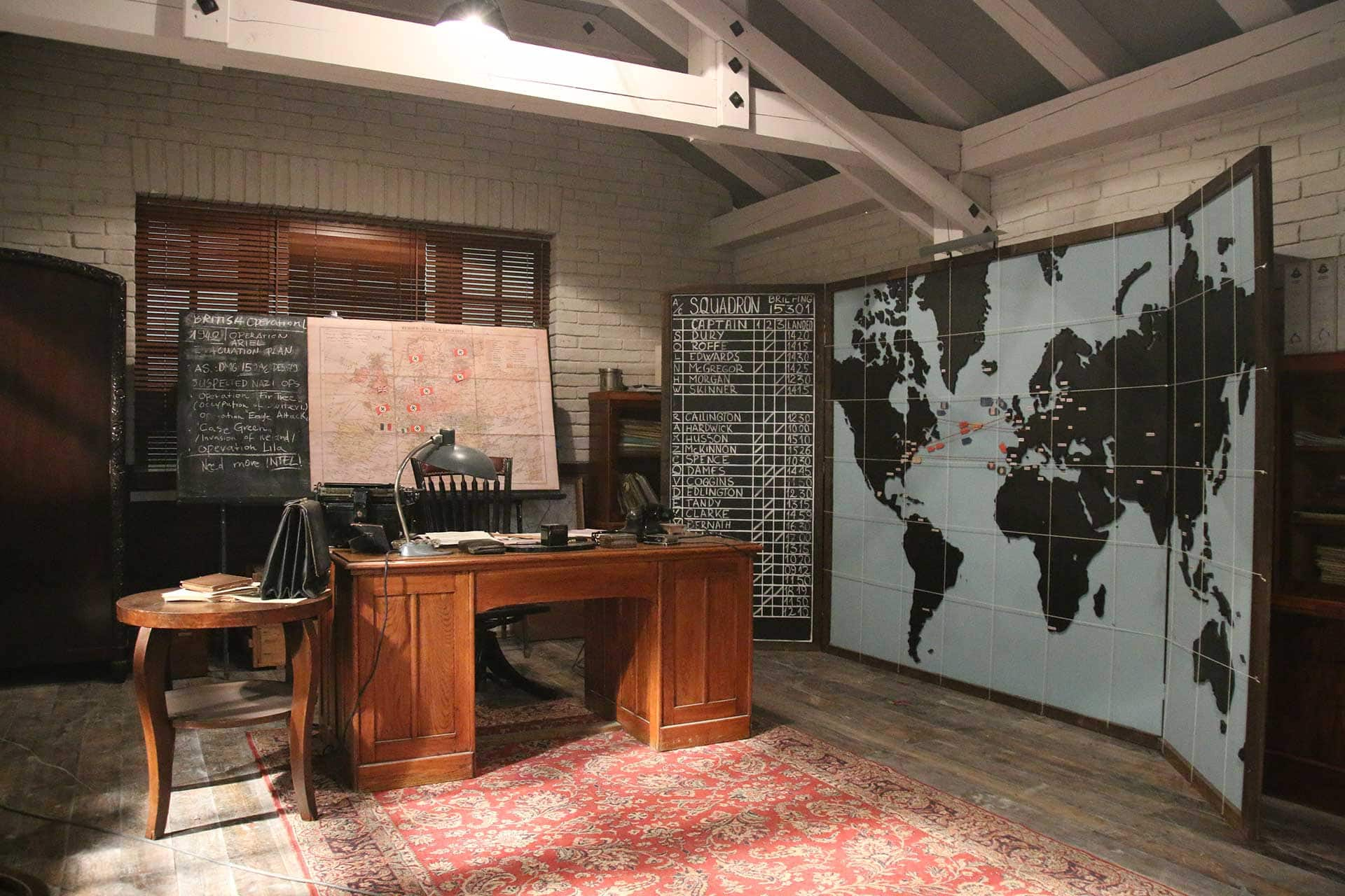 Sinclair's desk. The map behind his desk is an overview of the war in Europe. The large map on the right is an overview of the various teams deployed around the world.
