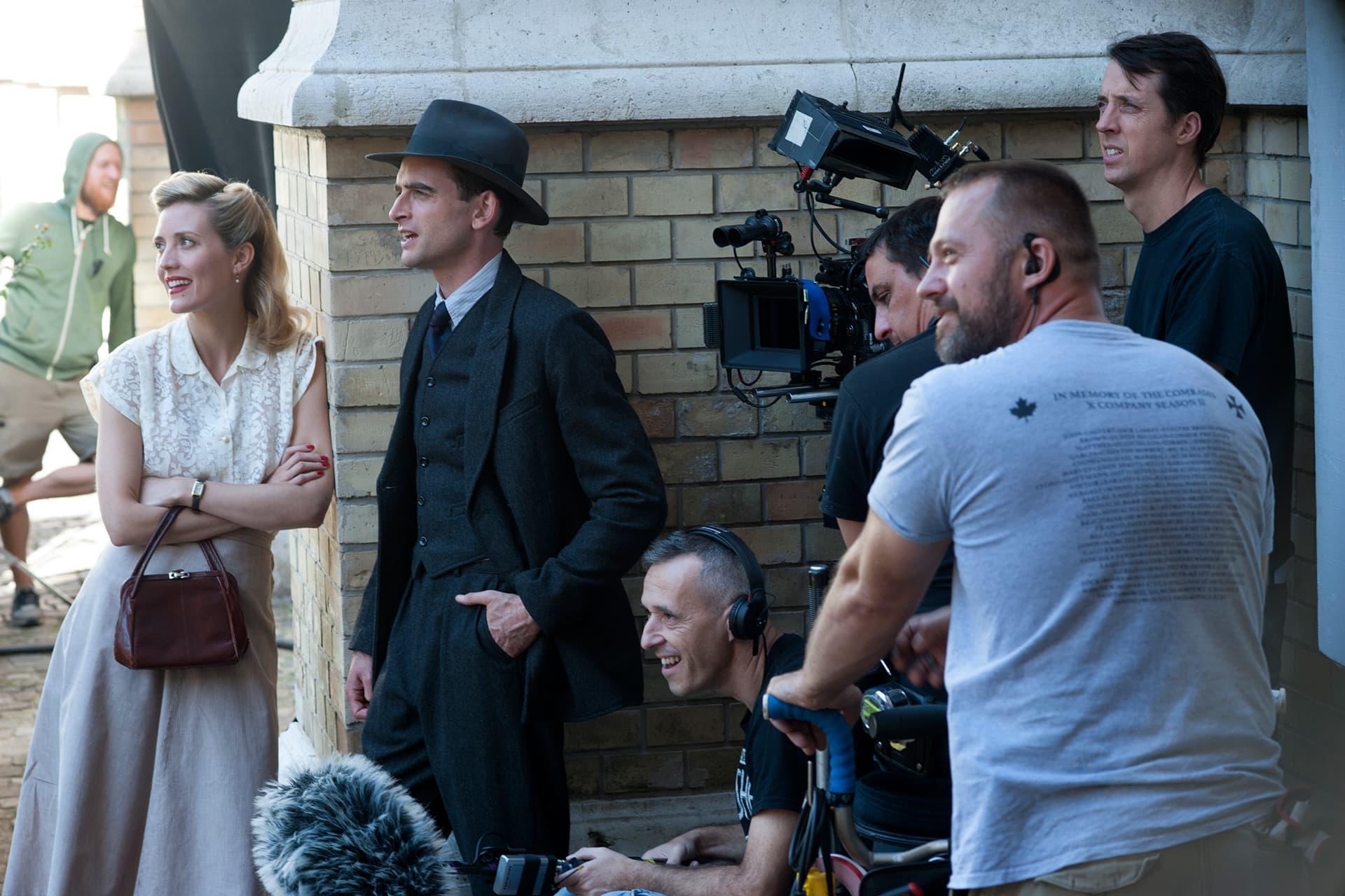 Evelyne Brochu (Aurora) and Jack Laskey (Alfred) with crew on the set of X Company Season 3.
